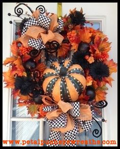 """A Spooky Surprise"" Halloween Wreath Adorable Halloween wreath filled with lush fall leaves, black Gerbera daisies, glittering sprays and ornaments, designer ribbon, and a whimsical pumpkin. This stunning wreath measures approx: 26"". Free US shipping on all Halloween wreaths!"