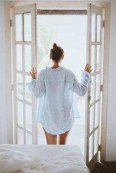 フリー写真 寝起きで扉を開ける後ろ姿の女性