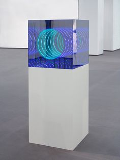 Artwork by Hans Kotter He uses LED lights that shine behind a warped one way mirror. The backing mirror then duplicates the LED lights infinitely.