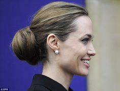 Schoolmarm chic: Angelina wore her hair in a tight bun and accessorised with a pearl choker and earrings