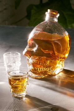 A glass skull decanter set that includes a pair of shot glasses. | 38 Badass Gifts For The Skull Lover In Your Life