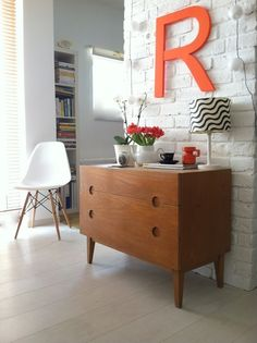 love this retro space, white painted brick walls, teak furniture.