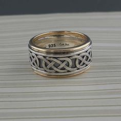 Celtic Eternity Knot Wedding Ring by Keith Jack.  Continuous Celtic Eternity Knot Design in 10K & Sterling Silver Ring. 10.5 mm wide and stamped .925 (Sterling Silver).  Oxidized background polished design & edges.  Sizes 8.5 or 9.5  Nicely boxed with silver cloth.