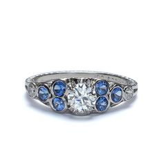 Delightful Art Deco Engagement ring. An Old European cut Diamond weighing 0.46 cts and certified by the GIA as J color and VS2 clarity (Report # 5181194183) is set in a low dome accented with bright, bezel-set Montana Sapphires (6 = 0.35 cts) and a pair of Old Mine Cut Diamonds (total weight 0.08 cys, HI color and SI clarity). Embellished with hand engraved wheat, palm, and scroll motifs, this unusual and stunning engagement ring is a a size 6 3/8 and stamped with the maker's mark of W.R…