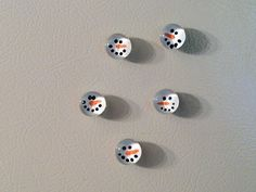 "Snowman Magnet Marbles- Paint face on flat side of clear flat-bottom marbles with acrylic craft paint using a toothpick.  Dry for two hours.  Add a layer of white paint over the faces, dry, & add 2nd layer, & dry.  Add a layer of clear varnish. Finally glue a 1/2"" round magnets on.  Great photos on the site."