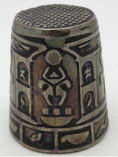 Dedal de metal con motivos egipcios.