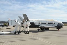 A recovery crew works on the X-37B space plane shortly after the spacecraft landed at Vandenberg Air Force Base in California on Oct. 17, 2014. The robotic X-37B spacecraft spent 674 days in orbit.