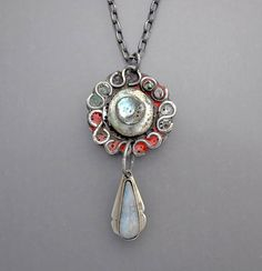A sterling silver necklace with a natural Australian boulder opal cabochon on a hand fabricated silver medallion with richly colored enamel work. The chain length is 16 and the pendant drop is 2 - 1/2