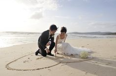 There are many different ways of getting your beach wedding photos taken. Drawing hearts in the sand is one of the favorite ways.