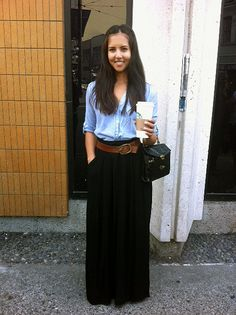 Great style with her black maxi skirt, white top and khaki scarf ...