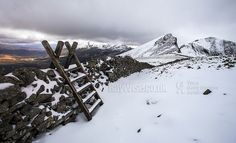 A famous view in Snowdonia, looking towards Nantlle Ridge from a stile and a snowy landscape on Y Garn.