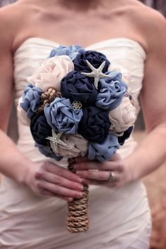 Unique, nautical and elegant, hand-sewn, large, fabric bridal bouquet, with or without rhinestone and starfish embellishments. Navy, blue and champagne flowers with a rope handle and nautical knots throughout the flowers for added nautical touch. Raw fabric edges with frayed ends are part of the aesthetic. Made with luxury chiffon and organza fabrics and high quality brooches. Measures approximately 13.5-14 tall with 9 diameter. Perfect bouquet for your nautical, yet elegant and classy…