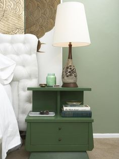 A hunter-green nightstand is the perfect fit for this serene bedroom by Emily Henderson. Sage-green walls allow the nightstand to pop without taking away from the gold hue found on the screen.