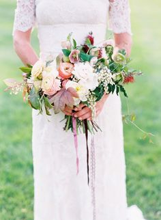 hand-tied bouquet featuring ranunculus, peonies, pieris and foliage by Kelly Lenard