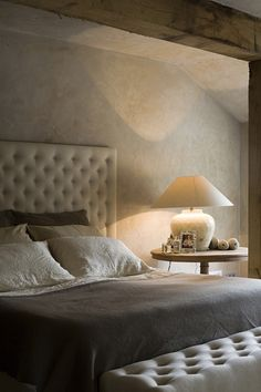 Masculine Bedroom with Grey and Cream Linens and Headboard, in a Converted French Farmhouse.