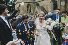 Bride & Groom confetti portrait outside the church - Classic Cotswolds Wedding At Temple Guiting Manor & Barns With Bride In Bespoke Blush Gown By Jenny Lessin With Bridesmaids In Mink And Groom In Blue Suit By Beggars Run With Images by John Day Photography