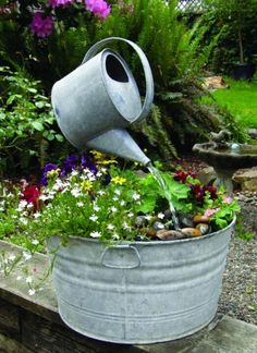 Watering can fountain with plants in old galvanized tub