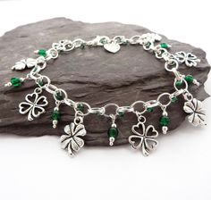 """<p>This lucky four leaf clover charm bracelet makes great St Patrick's Day Jewellery featuring emerald green beads and shamrock charms. </p><p> </p><p>Details: </p><p>This chunky charm bracelet is a real statement piece made using a chunky silver plated chain with lobster clasp. Each bracelet features silver plated shamrock charms and sparkling emerald green glass beads.</p><p> </p><p>Sizing </p><p>The bracelet measures approximately 20cm (almost 8"""") and is designe"""