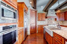 Custom cabinets in kitchen with beautiful wood beams on ceiling