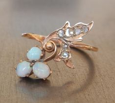 This lyrical ring from pre-1917 Imperial Russia features three aqua toned opals and six small rose cut diamonds in a 14k rose gold Art Nouveau flower and leaf setting. Rare, delicate and exquisite! Russian hallmarks stamped on side of band