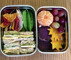 easy bento ideas. turkey sandwich, root veggie chips, snap peas, tangerine, grapes, purple sweet potato, and dried mangos cut into sun shapes.