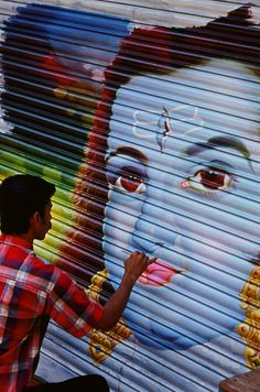 Poster artist Rajan painting a store shutter with the blue-faced Lord Krishna. © 2005 Salaam Shalom Productions Inc.