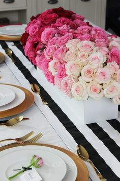 How to create an ombré centerpiece using flowers in shades from dark red to pale pink. We paired our floral arrangement with a black and white striped runner, different shades of pink napkins and gold flatware.