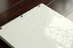 Custom white acrylic portfolio with engraving and cut-out treatment close up