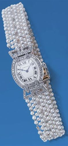 Edwardian Seed Pearl and Diamond Wristwatch, Cartier  Platinum, 18 kt. gold, centering a tonneau-shaped matte silver dial with black Roman numerals, edged by rose-cut diamonds and flanked by flared lugs set with rose-cut diamonds, accented by a rose-cut diamond crown, completed by a seven row pearl bracelet, pearls approximately 2.5 mm., terminating in a deployant gold buckle, the rectangular platinum clasp outlined with rose-cut diamonds, centering 6 old European-cut diamonds.
