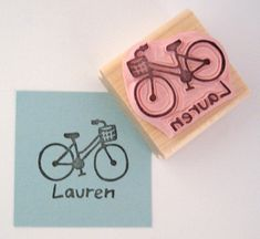 Hand carved stamp in the shape of a bicycle with basket with one name personalization, please specify name at checkout. Give your craft items a personal touch with this hand carved stamp. Use it for scrapbooking, cards, gift tags, wrapping paper. Stamp it on fabric, wood projects, walls