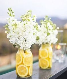 Easy DIY centerpiece - mason jars with lemon slices, white hydrangeas and a pop of greenery. These would look great on a lemonade stand for your guests before or after your ceremony