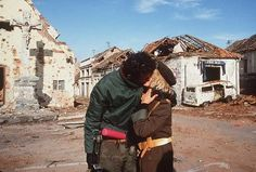 A Serbian couple in Vukovar, weapons in hand, celebrate survivng another day.