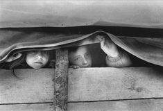 wo Kosovo Albanian refugee girls look out from the inside of a wagon in Morina (Albania), April 1999