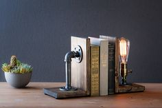 Industrial Bookend Lamp - Steampunk Lamp - Table Lamp - Edison bookend Lamp - Vintage Light - Pipe Lamp - Bedside Lamp - Rustic Lighting ★Bulb Included. ★Choose Socket & Wood Color. ★Includes both bookends pieces.  LAMP DETAILS: ➼HANDMADE in the USA  ➼Pipe features made from real steel.  ➼Measures 5 1/2W, 10 1/2H.  ➼Cord length 8F.  ➼Socket 60 watt max.  ➼Classic 40 watt marconi filament Edison bulb included in purchase.  ➼Choose from 3 wood base finishes. ➼All electrical compon...