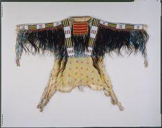 Itazipacola Lakota (Sans Arc Sioux) Man`s shirt, circa 1870, Materials:Hide, human hair, glass bead/beads, paint, vermilion/cinnabar, wool cloth, porcupine quills, metal cones, sinew / Techniques:Sewn, lazy/lane stitch beadwork, painted, quill-wrapped (flat)