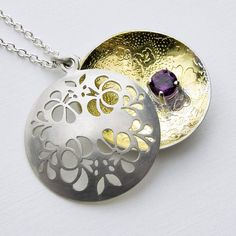 Floral open locket with gold and a rhodolite gem - open view.