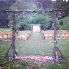 Outdoor ceremony in an open field. Intimate space created using log arbors wrapped in vines. The brides grandmother's quilt hangs behind where they say their vows. Rustic country wedding. Romantic.