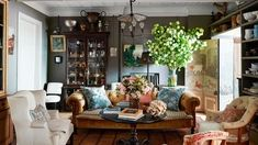a 19th century armchair  sofa  by john derian for cisco brothers and antique french armchairs form a seating area in the living room