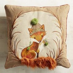 A friendly fox is sending you warm winter wishes. Our cozy pillow features our woodland friend in silk-stitch embroidery, appliqued brown check fabric, fuzzy green pompoms and the fluffiest, faux fur tail around.