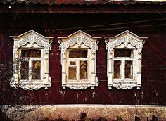 Wall of wooden traditional russian house with windows and carved frames and pattern