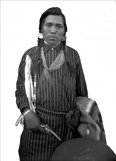 Mas-a-lee, a Native American man on the Flathead Indian Reservation in western Montana, stands holding a gun in his right hand. He holds a wide-brimmed hat and a patterned blanket in his left hand. His empty holster hangs around his waist. He wears a long striped shirt, large round earrings, and his hair in braids. He also has a scarf tied around his neck. Date 	[between 1905 and 1907?]: