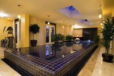Swimming Pool Ideas : This indoor pool looks like it has come right out of the movies. With checkered swimming pool walls, dark green lush planters all around, and yellow-golden tones of light illuminating the whole area, it is just perfect and mystical. Swimming Pool Photos, Cool Swimming Pools, Swimming Pool Designs, Cool Pools, 8 Pool, Small Indoor Pool, Indoor Swimming Pools, Outdoor Pool, Backyard Pools