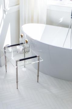 A nickel and lucite accent table sits on white herringbone floor tiles beside an oval freestanding bathtub positioned beneath a window dressed in white curtains. Tiny Bathrooms, Beautiful Bathrooms, White Master Bathroom, Master Bedroom, Paint Colors For Living Room, Room Paint, Bathroom Renovations, Interior Design Living Room, Freestanding Bathtub