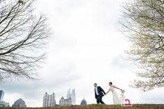 Bride and groom running around Atlanta Midtown skyline at intimate Piedmont Park wedding from Destination + Atlanta wedding photographers Matthew Druin + Co. NO TRAVEL FEES IN THE US!