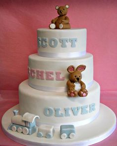 A gorgeous 3 tier Christening cake with hand made teddy, bunny and train. letters hand cut and embossed.