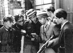"""Eugeniusz Lokajski """"Brok"""": Grupa powstańców z kompanii """"Koszta"""" czytających (prawdopodobnie) niemiecką ulotkę propagandową na ul. Sienkiewicza pod kamienicą nr 14  sierpień 1944"""