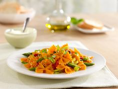 1 box Barilla® Veggie Farfalle  4 tablespoons extra virgin olive oil  1 diced leek  1 bunch asparagus (sliced thin on a bias)  2 roasted red bell peppers* (diced)  Salt and black pepper to taste  ½ cup grated Parmigiano Reggiano cheese  5 leave basil (cut chiffonade style)