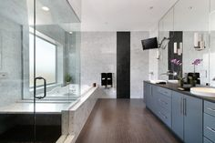 Marble wrapped bathroom stands muted blue cabinetry over rich dark wood flooring. Dual vanity stands beneath full height mirror, while glass shower enclosure abuts a large jacuzzi tub beneath smoked glass window.