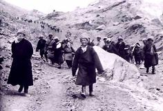 Flight of the 14th Dalai Lama. An unusual photograph depicting the 14th Dalai Lama walking through the mountains in his flight from Tibet in 1959. Seen on the left, wearing his distinctive spectacles, he is joined by his brother and countless followers, his bodyguards consisting of Khampas who comprise the warrior class in Tibet.  The flight of the Dalai Lama has been chronicled and undoubtedly it was an arduous journey but here he seems relaxed, calmly walking on a rather wide mountain…