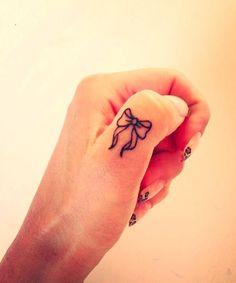 Tatuaggi dita: fiocchetto sul pollice